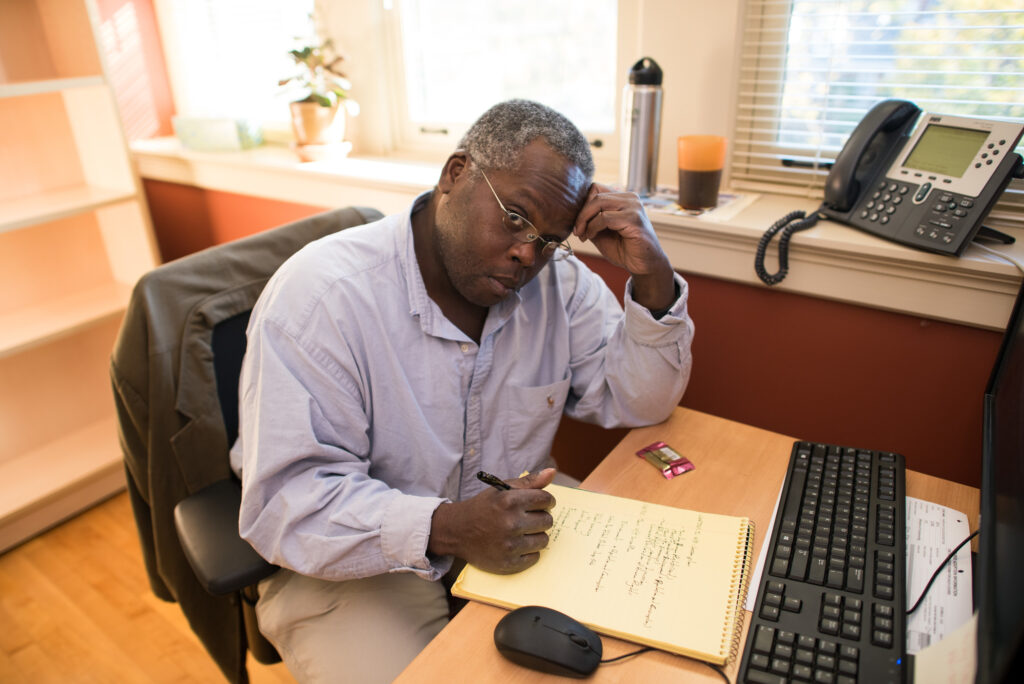 A Black male faculty member takes notes at a desk with a computer