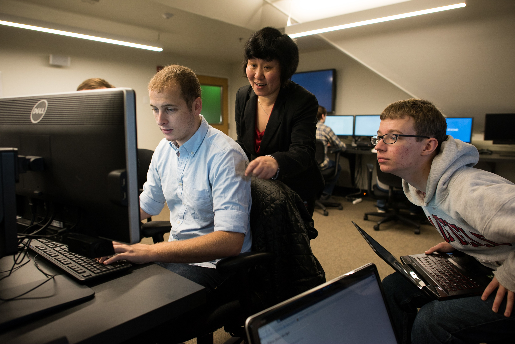 A female faculty member coaches a male student working at a computer from behind, while another male student looks on