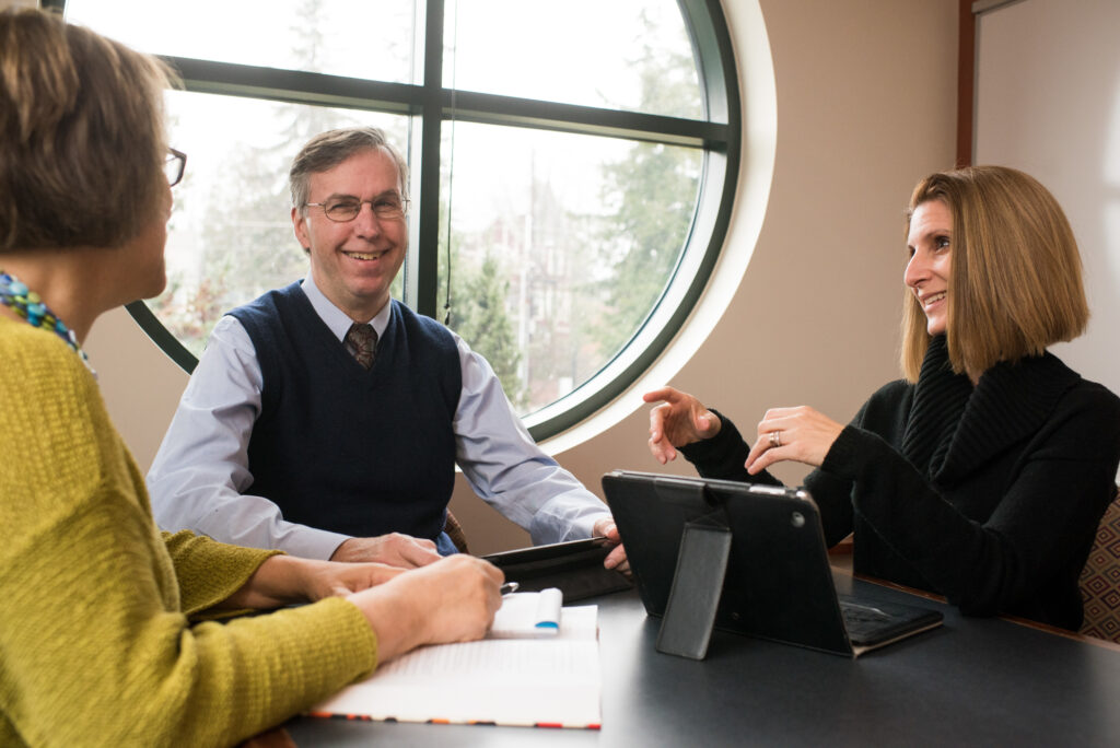 Three faculty members (two women and a man) talk at a conference table. One of the women gestures while speaking.