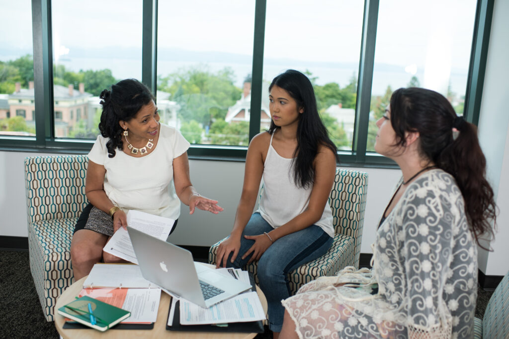 A woman of color faculty member confers with two women students around a table covered with papers and a laptop