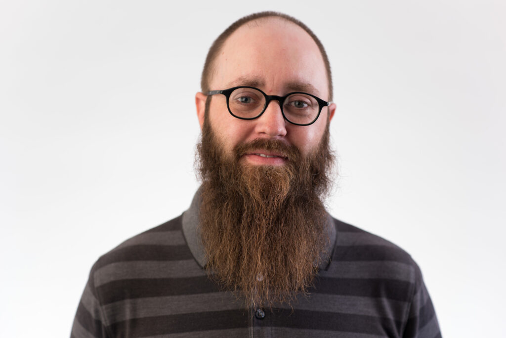 A white man with dark hair and a long beard wearing glasses