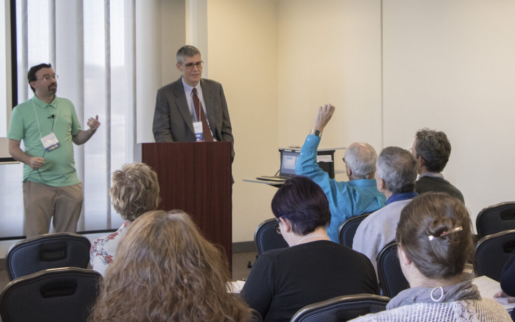 A male faculty member presents to an audience of professionals. Another man faces the audience, gesturing.