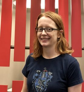 A red-haired white woman with glasses in front of a geometric background