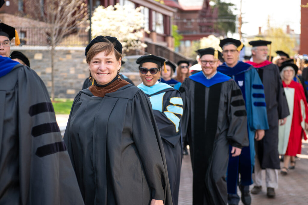 A line of faculty members wearing academic regalia and standing on a patio
